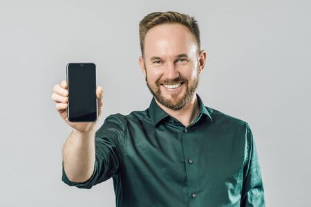Buy this phone. Portrait of cheerful attractive white male with beard, pulling hand towards camera and showing smartphone over gray background Banco de Imagens