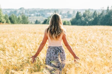 Young woman in dress walking along cereal field. Concept of happiness, loneliness, summer, countryside vacation Banco de Imagens