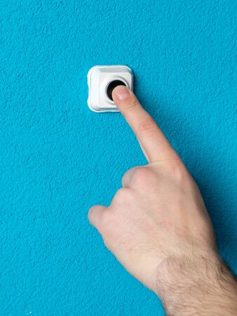 Close-up of man's hand pressing the button of doorbell on blue wall Archivio Fotografico - 131407784