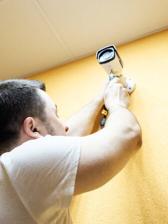 Professional CCTV technician working. Man installing surveillance ip camera for home security Banco de Imagens