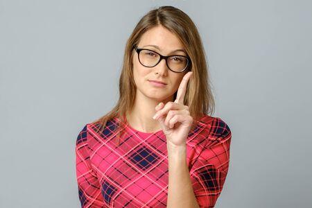 Grave aislado sobre fondo gris mujer mirando a la cámara y hacer una señal de advertencia, amenazando con el dedo