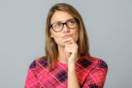 Young beautiful wearing glasses over gray background with hand on chin thinking about question, pensive expression. Doubt concept