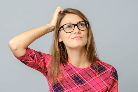 Portrait of nice attractive beautiful confused lady with eyeglasses touching head don't know what to do. Isolated over gray background