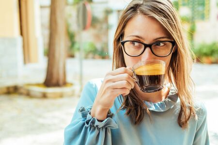 Young woman sitting at outdoor cafe with a cup of coffee and looking away