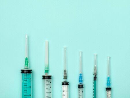 Set of medical syringes on colorful background