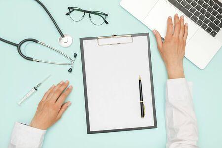 Doctor sitting at blue office desk and working Reklamní fotografie