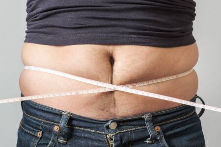 Fat man check out his body fat with measuring tape Reklamní fotografie