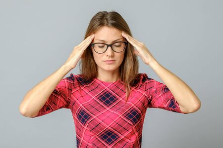 Young woman with a headache touching head. Isolated on gray background