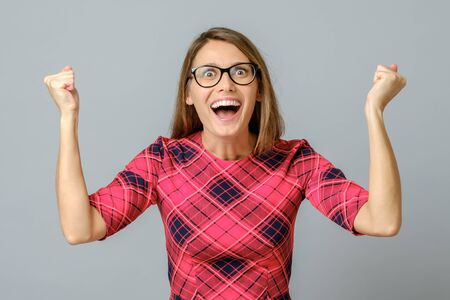 Happy girl celebrating her success with raised arms isolated on the gray background