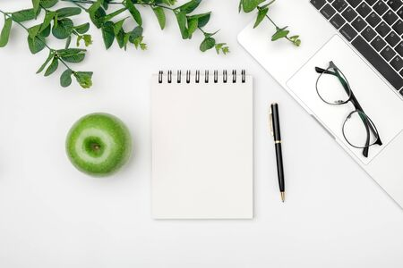 Minimal workplace with laptop and blank notepad on white background. Top view. Flat lay Reklamní fotografie