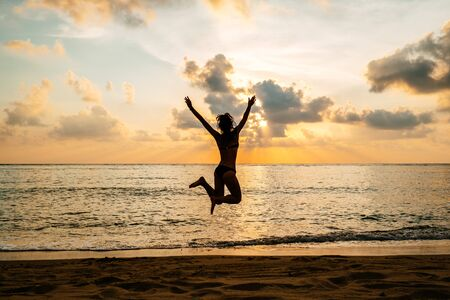 Silhouette of happy joyful woman jumping and having fun at the beach against the sunset. Freedom and vacation concept Reklamní fotografie