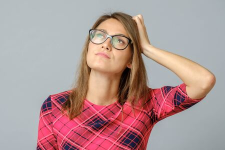 Portrait of nice attractive beautiful confused lady with eyeglasses touching head dont know what to do. Isolated over gray background