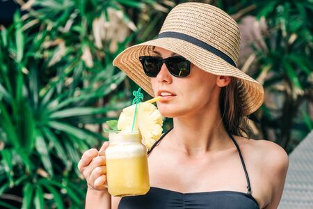 Relaxed woman in bikini enjoying tropical resort, drinking pineapple cocktail