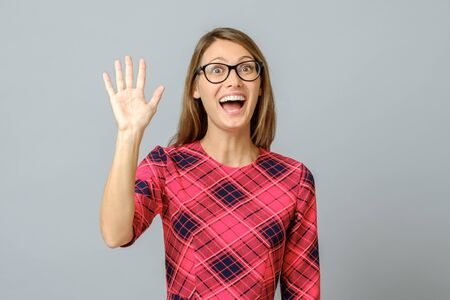 Young beautiful woman wearing red dress standing over gray isolated background waiving saying hello. Friendly welcome gesture