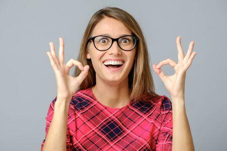 Portrait of nice lady showing okey symbol isolated on gray background