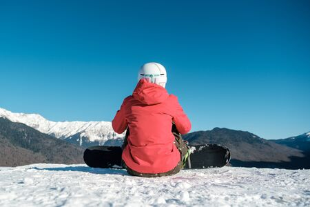 Rear view of snowboarder in sportswear with equipment resting on top of ski slope enjoying view
