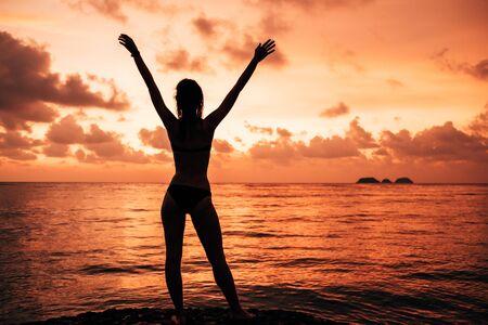 Damensilhouette mit erhobenen Armen gegen ruhigen Sonnenuntergangsstrand Standard-Bild