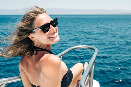 Happy smiling beautiful young girl portrait in sunglasses on the yacht or boat on the coast with sea on background. Paradise island cruise 版權商用圖片