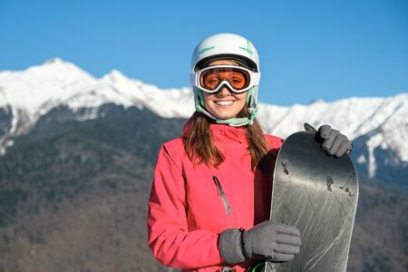 Portrait of a sportswoman wearing helmet and mask with snowboard in hand looking at camera, smiling, enjoying sunny frosty day Stock Photo