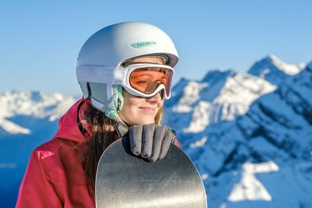 Woman snowboarder standing with snowboard. Closeup portrait of cheerful snowboarder at top of ski slope
