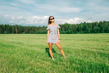 Beautiful girl in dress on green field. People and nature concept 版權商用圖片