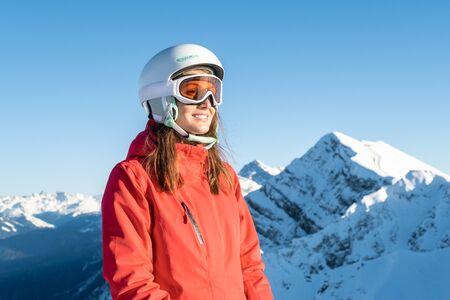 Closeup portrait of woman in helmet and mask with on ski resort. Winter adventure concept