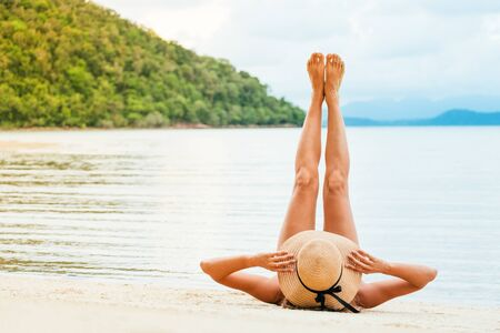Beautiful woman lying on a tropical beach with legs raised up high in the air. Blue sea in the background. Summer vacation concept