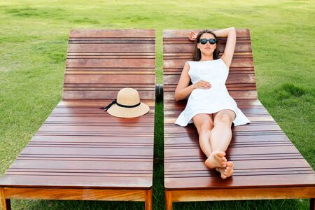 Beautiful young woman lies and rests on a wooden deckchair
