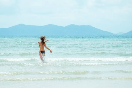 Happy carefree woman wearing bikini having fun on summer vacation. Funny girl running with open arms in ocean water at tropical holiday 版權商用圖片