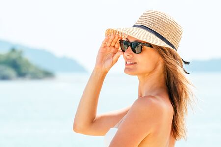 Portrait young woman wearing a straw hat on beach with sea in background