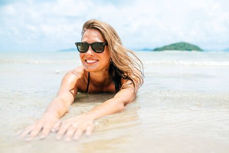 Beautiful woman with perfect body lying down on the beach sand, wearing black bikini and sunglasses, tanning on a beach resort, enjoying summer vacation 版權商用圖片