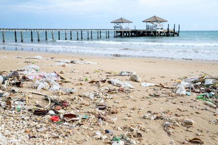 Spilled garbage on the beach. Empty used dirty plastic bottles. Environmental pollution. Ecological problem Stock Photo