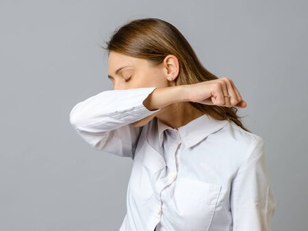 Sneezing woman medical nurse or doctor doing elbow sneeze. Isolated on gray background