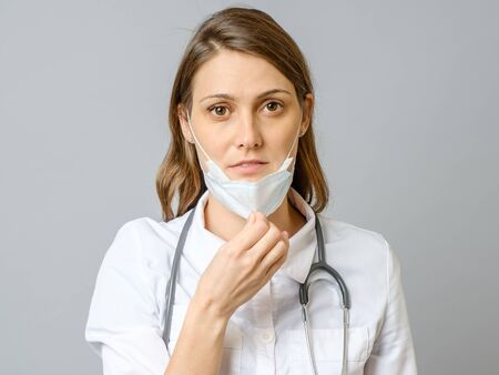Portrait of tired young doctor taking off medical face mask isolated over gray background