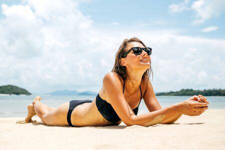 Beautiful woman with perfect body lying down on the beach sand, wearing black bikini and sunglasses, tanning on a beach resort, enjoying summer vacation Archivio Fotografico