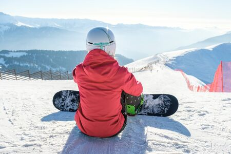 Snowboarder girl sits with board at the ski slope in mountains. Back view. Winter landscape 版權商用圖片