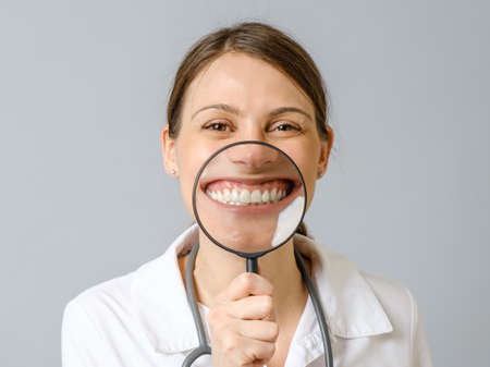 Funny image of happy excited female doctor smiling and showing teeth through a magnifying glass over gray background