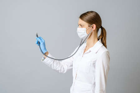Doctor woman wearing protective mask using stethoscope isolated on gray background