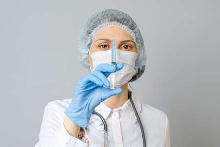 Portrait of young woman in medical uniform, protective mask and cap with medical syringe in hand. Isolated on gray background 写真素材