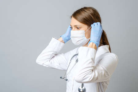 Portrait of a young female medical doctor or nurse putting sterile mask isolated on gray background