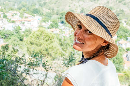 Sunny lifestyle portrait of young hipster woman, wearing straw hat. Portrait with valley landscape backgroung