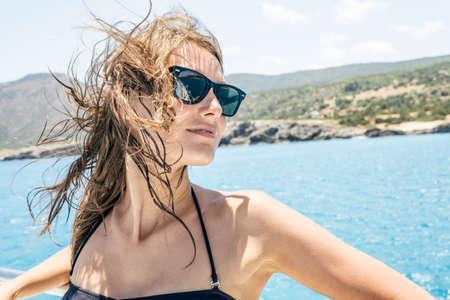 Happy female tourist having fun on sailboat. Summertime sailing vacation. Beautiful woman outdoor in bikini