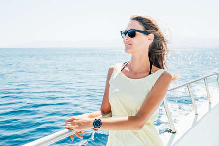 Beautiful young brunette girl in a yellow dress. Summer trip on a yacht on the sea or ocean