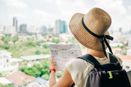 Back side of traveler girl searching right direction on map, traveling along Asia. Freedom and active lifestyle concept