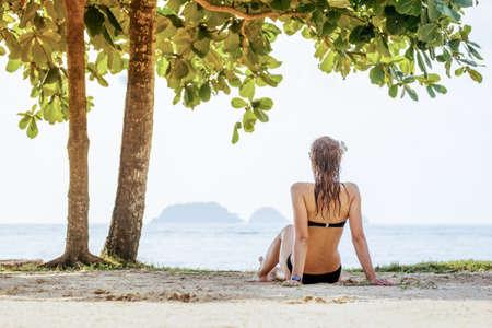 Sexy fit woman in bikini sitting on beach
