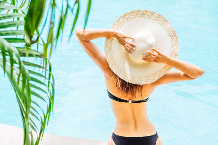 Back view of woman in swimsuit and hat near the pool