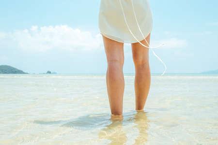 Low angle woman walking barefoot on beach