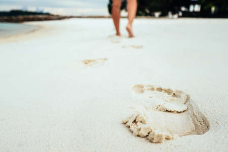 Trail barefoot feet in the sand on a beautiful beach