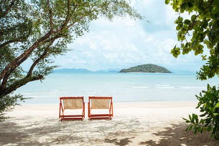 Two sunbeds on a beautiful sandy beach with clear water and island on background