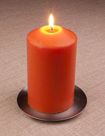 Burning candle over textile background Stock Photo - 14016483
